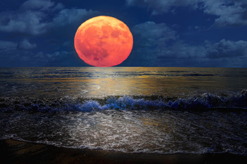 Beautiful landscape of full moon rising in the beach