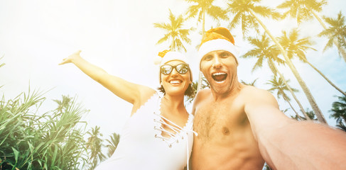 Happy smiling couple take selfie photo in Santa hats under the palm trees. New Year tropical vacation