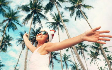 Happy smiling woman in Santa hat stay under palm trees. Christmas holiday on tropical island