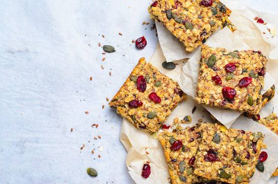 Granola Bars, Superfood Homemade Snack, Healthy Bars with Cranberry, Pumpkin Seed, Oats, Chia and Flax Seed on bright background