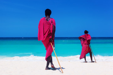 Foto op Plexiglas Zanzibar Two maasai warriors looking on ocean.