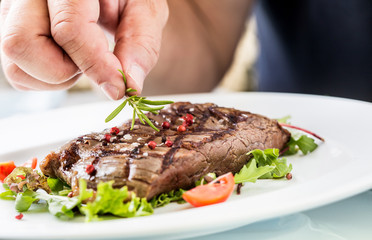 Chef prepared beef flank steak with vegetable decoration.