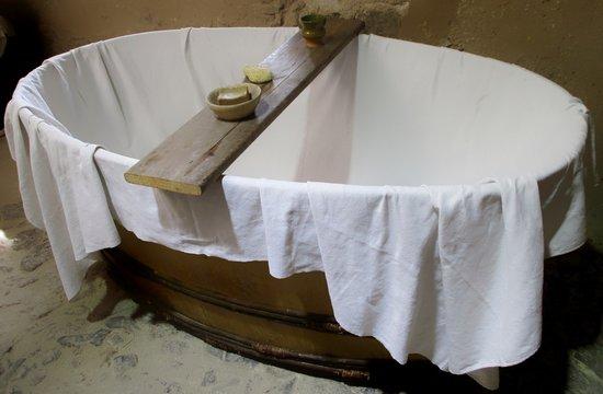 baignoire en bois garnie d'un drap et accessoires de bain comme au moyen âge