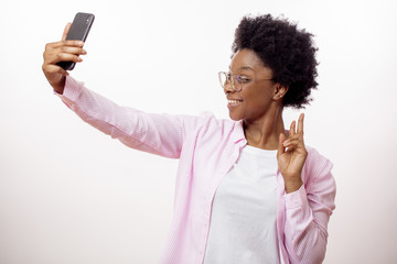 cheerful woman posing to her smart phone. close up side view photo. afro girl having fun with smart phone