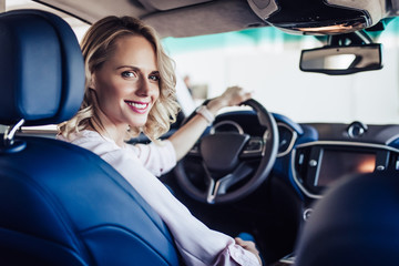 smiling woman sitting in the car