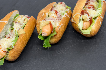 Fototapete - delicious homemade hot dogs on black slate close up photo