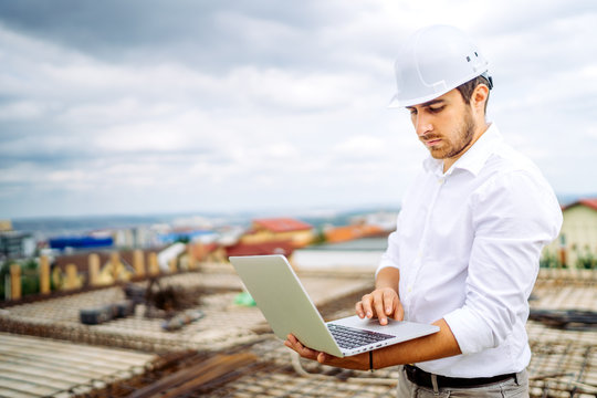 Supervisor engineer using laptop on construction site. Industry details