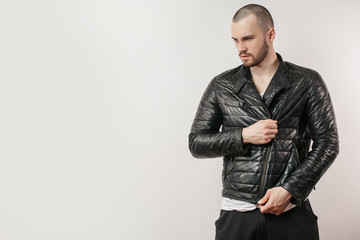 sportsman trying on new stylish jacket.. serious male putting on warm outfit. copy space. close up photo. biker in trendy clothes looking aside