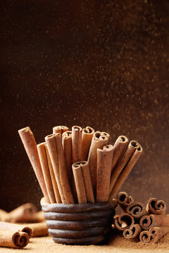 Cinnamon sticks in bowl and powder on brown background. Aromatic spice.