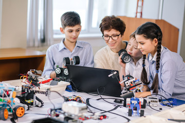 group of happy kids with their female adult science prof with tablet pc computer programming electric toys and robots at robotics hobby club
