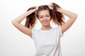 funny girl in white t-shirt making two ponytails with her brown hair isolated over white background. entertainment, free time, lifestyle
