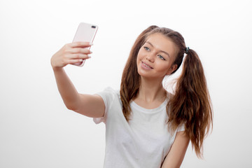 attractive girl with two funny ponytails taking picture of herself, free time, device, hobby, spare time concepts. close up portrait