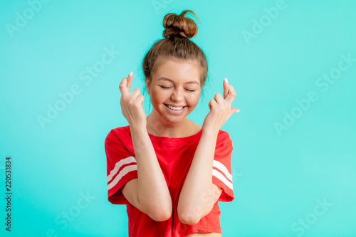 Glad Happy Woman Wears Red T Shirt Keeps Fingers Crossed