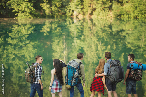97474a74db29 tired but happy tourists are standing in frint of the beautiful lake. wild  life concept. environment concept