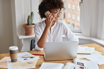 View of cheerful executive manager shares opinions about startup, has phone conversation, works on financial report, sits in front of opened laptop computer, makes graphics, looks happily aside