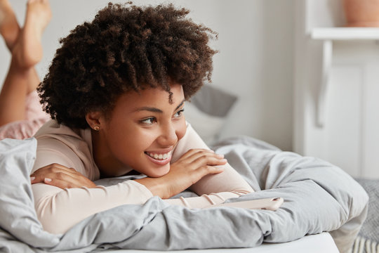 Close up shot of relaxed beautiful happy dark skinned young female with curly hair, lies in comfortable bed, being in good mood after unforgettable night with husband, enjoys day off or weekend
