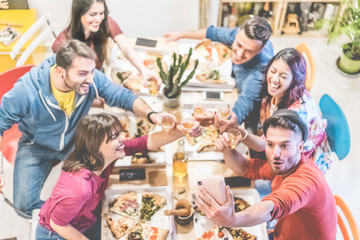 Happy millennials friends taking selfie instant photo at pizza home party