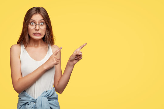 Oops, come and look there! Lovely young woman feels worried and ashamed, points with both index fingers at upper right corner, isolated over yellow background, makes mistake and looks awkward