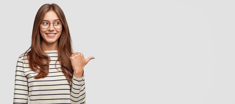 Indoor shot of pretty young brunette woman with dark hair, notices funny scene left aside, points with thumb, being in good mood, has joyful and carefree expression, isolated over white background