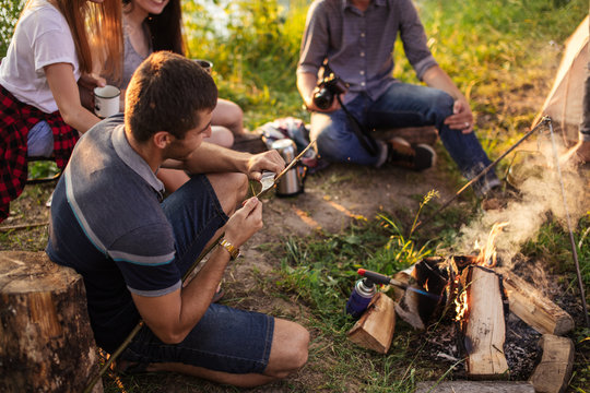 pleasant man is cutting a wooden stick with knife for hunting while his friends are sitting near the bonfire