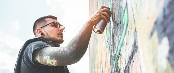 Tattooed graffiti writer painting with color spray his picture on the wall