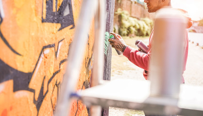 Tattooed graffiti writer painting with color spray his picture on the wall - Contemporary artist at work