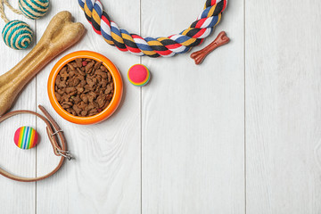 Bowl with food for dog or cat and accessories on wooden background. Pet care Wall mural