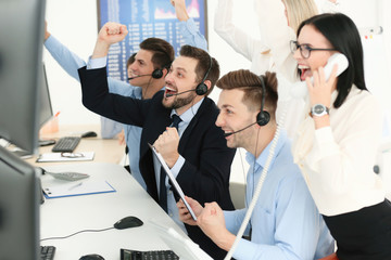 Excited stock traders working in office