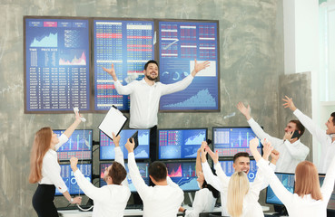 Excited stock traders celebrating success in office