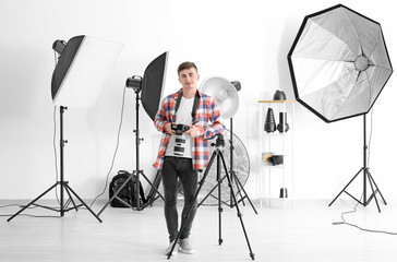 Young male photographer working in studio