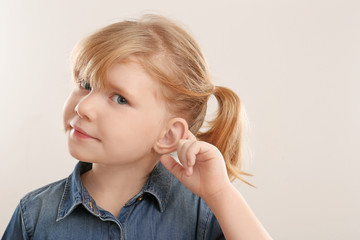 Cute little girl with hearing problem on light background