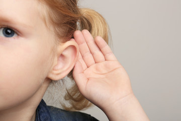 Cute little girl with hearing problem on grey background
