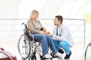 Male doctor taking care of mature woman in wheelchair indoors