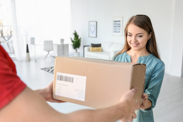 Young woman receiving parcel from courier