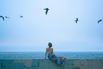 woman in dress in front of ocean