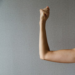 Woman holding a raised hand in the fist