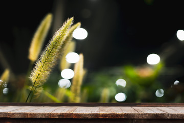 Selective focus of wooden table in front of Grass flower with nature background, can used for display or montage your products.