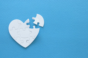 Top view image of paper white heart puzzle with missing piece over blue background. Health care, donate, world heart day and world health day concept.