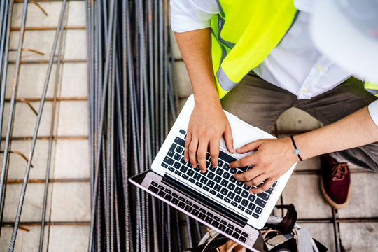 close up details of engineer working on laptop on construction site
