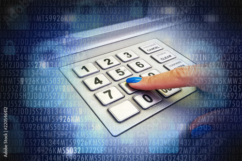 Close-up of woman's hand introducing pin code at ATM machine for