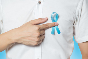 Men's healthcare concept - close up of male hand pointing to light blue ribbon for prostate cancer at left chest on blue background.