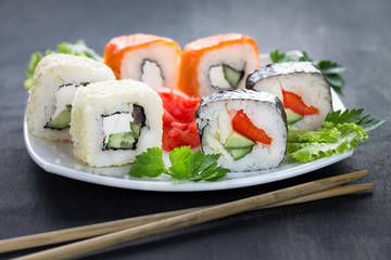 Sushi on a square white plate with parsley and chopsticks. Close up. Gray background