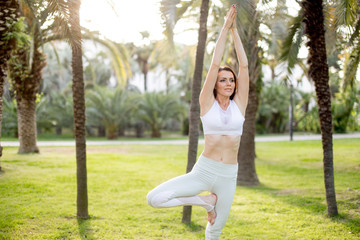 Woman meditating in yoga tree pose at the green grass glade. Motivation and inspirational fit and exercising. Healthy lifestyle outdoors in nature, fitness concept.