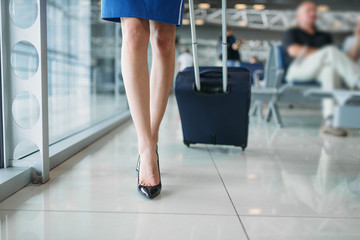 Stewardess legs and suitcase in airport hall