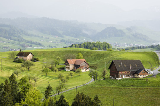 Foggy spring day with farms in the Entlebuch in the canton of Lucerne in central Switzerland