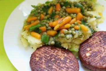 Kartoffelpüree mit Gemüse und vegetarischen Frikadellen auf grünem Hintergrund
