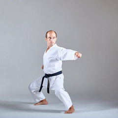 A kick is trained by an athlete in a formal karate exercise