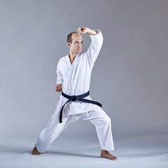 On a gray background the athlete trains the block with his hand in a formal karate exercise
