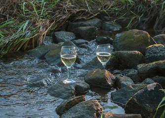 Weißweingläser in kräftigen Farben auf Steinen im fließenden Wasser