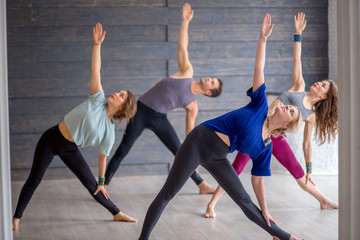 Group of caucasian young sportive people wearing sportswear working out against grey wall, doing yoga or pilates exercise. Standing in Utthita Trikonasana, extended triangle pose. Full length